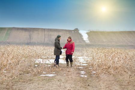 dandose la mano: Dos hombres agitando las manos en las tierras agr�colas en �poca de invierno