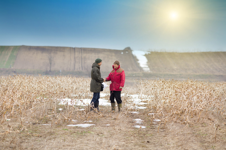 shaking hands: Two men shaking hands on farmland in winter time