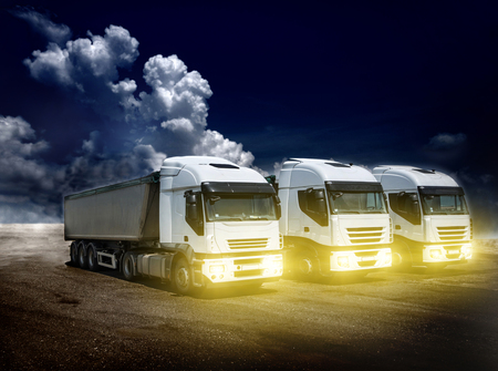 dramatic sky: Three trucks with trailers parked on field with dramatic sky in background