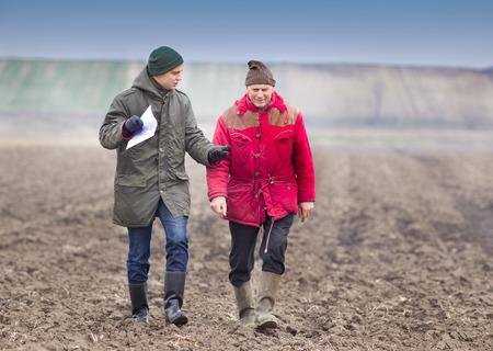 two people talking: Two farmers walking on plowed field in winter time