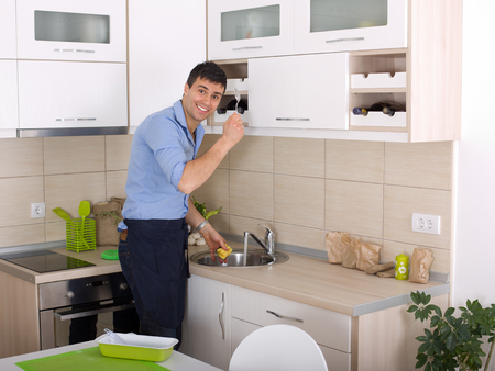 Happy young man washing the dishes after cooking