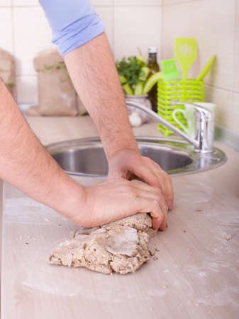 Male hand kneading dough of wholemeal bread on kitchen counter photo