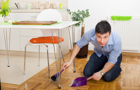 under the surface: Young man on knees holding broom and dustpan under table in kitchen