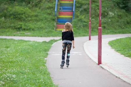 blading: Young blonde girl with dreadlocks skating in park