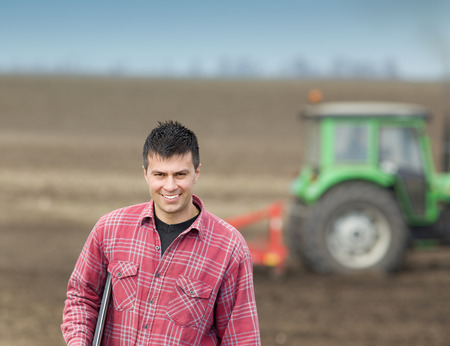 farmers: Young happy farmer carrying laptop under armpit on field, tractor in background