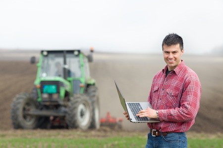 Young landowner with laptop supervising work on farmland, tractor in background
