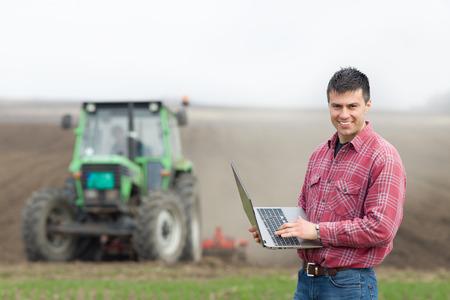 Jonge landeigenaar met laptop toezicht op het werk op landbouwgrond, tractor op de achtergrond