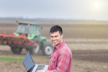 landowner: Young landowner with laptop supervising work on farmland, tractor in background