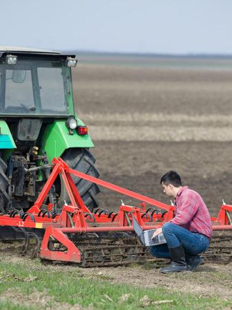 Jonge landbouwer werken op de laptop op landbouwgrond naast tractor