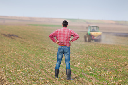 Young landowner stading with hands on hips and supervising work on farmland, tractor in background photo