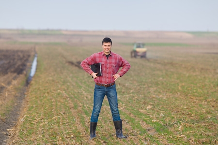 Young landowner with laptop supervising work on farmland, tractor in background photo