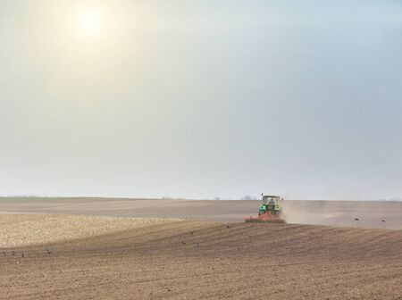 harrowing: Tractor harrowing soil on overcast in early spring