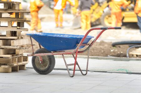 Dirty handcart standing on construction site, workers and machinery in background photo