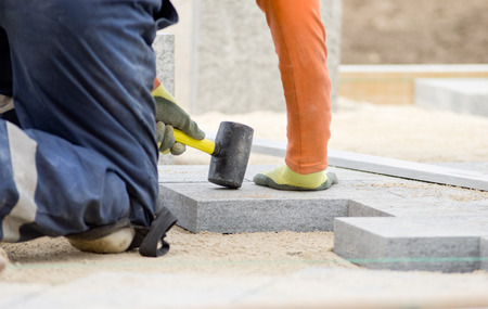 Paver hammering flagstones in sand for leveling future pavement