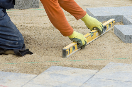 Craftsman leveling sand for installing flagstones for pavement