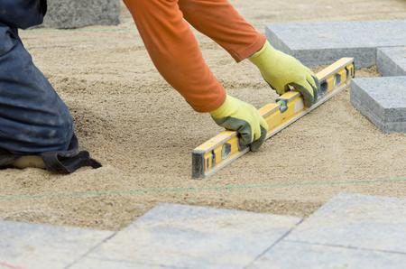 Artigiano livellare sabbia per l'installazione di lastre per pavimentazione Archivio Fotografico