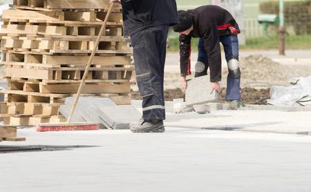 Operaio edile in vestiti di sicurezza per la pulizia del cantiere dopo l'installazione di lastre di pietra nella sabbia