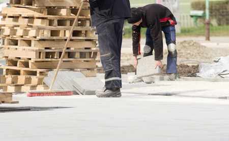 Construction worker in safety clothes cleaning building site after installing flagstones in sand Banque d'images