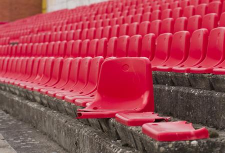 openair: Red broken seats on open-air stands on football stadium