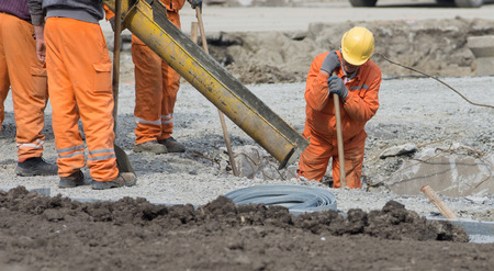 strret: Worker leveling concrete poured from mixer on construction site