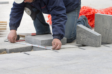 Construction worker measuring flagstone and preparing for cutting to fit in pavement