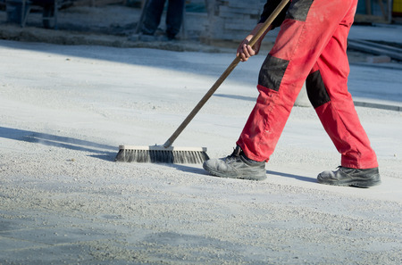 broom: Construction worker in safety shoes cleaning building site after paving work Stock Photo