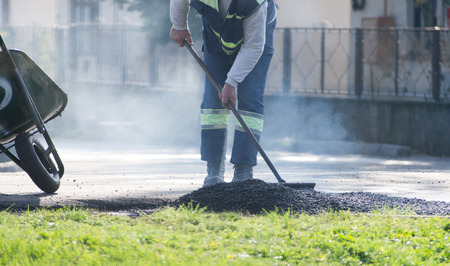 asphalting: Construction workers asphalting road in the city