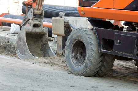 bagger: Excavator bucket digging ground for installing pipes at the street