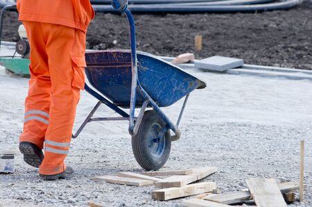public works: Construction worker pushing carts with cement on building site