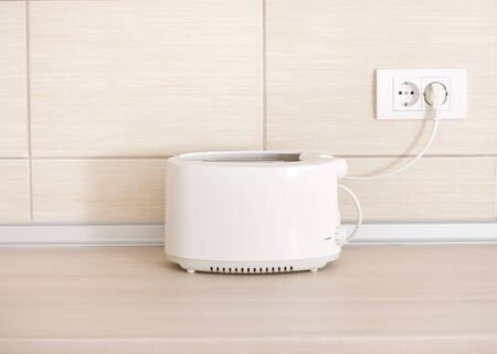 plugged: White toaster plugged in socket on kitchen countertop