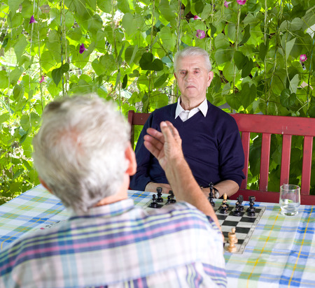 chess men: Two senior men talking in courtyard before chess match Stock Photo