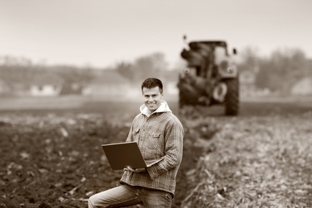 landowner: Young landowner with laptop supervising work on farmland, tractor in background, black and white image Stock Photo
