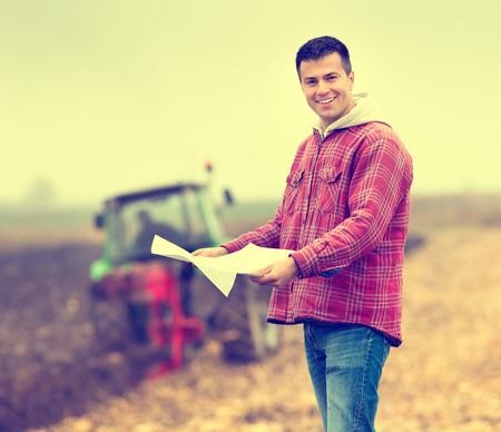 agricultor: Agricultor joven feliz con formas de préstamo bancario de pie en el campo, un tractor de fondo Foto de archivo