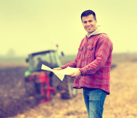 the farmer: Happy young farmer with forms for bank loan standing on field, tractor in background