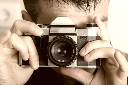 slr: Young man holding old fashioned slr camera
