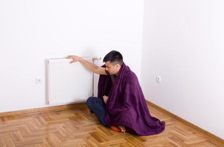 shiver: Young man covered with blanket sitting on floor and holding hand on radiator