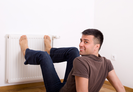 Young man heating his bare feet on radiator on wall photo
