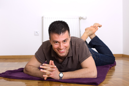 legs up: Attractive man lying on the floor on stomach  with legs up and looking at camera
