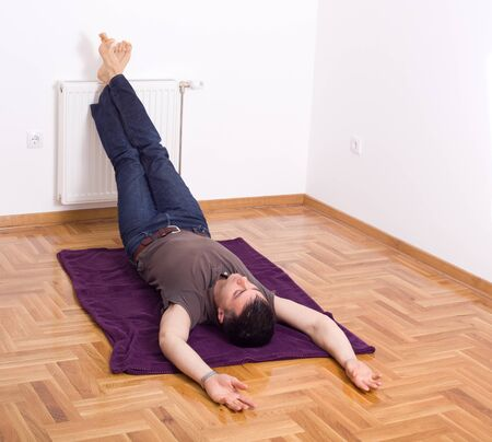 Man relaxing on the floor with his legs up on radiator on wall photo