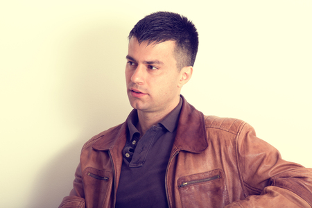 common sense: Portrait of young handsome guy in brown leather jacket sitting and looking at side