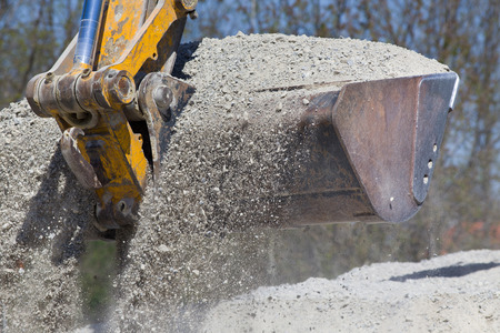 Close up of excavator bucket scooping gravel from pile for road construction Stock Photo