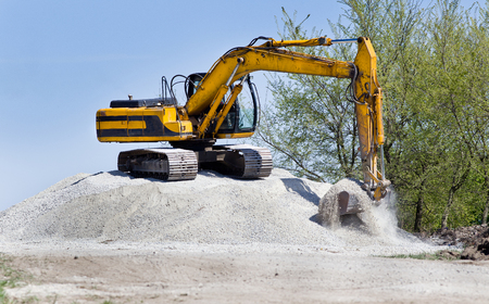 dredging tools: Excavator standing on top of gravel hill and moving gravel with scoop Stock Photo