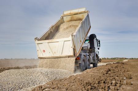 Propinas camión descargando grava en el sitio de construcción de carreteras