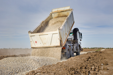 Tipping truck unloading gravel on road construction site