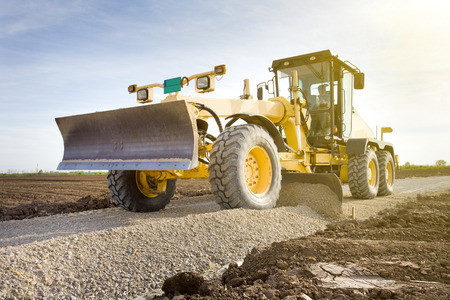 'earth mover': Grader leveling gravel on road construction site