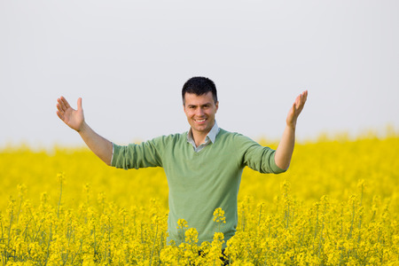raised arms: Satisfied businessman with raised arms standing in rapeseed field