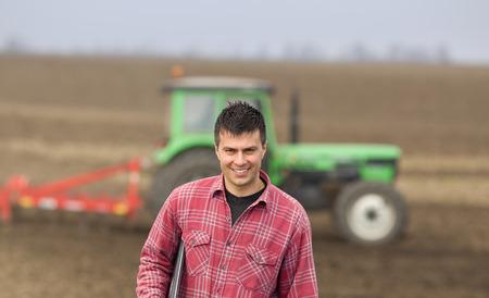 granjero: Granjero feliz joven llevando portátil debajo de la axila en el campo, un tractor de fondo