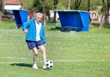 Old man in seventies kicking a soccer ball on the field