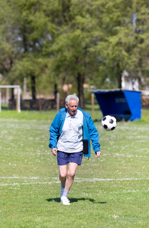 the seventies: Old man in seventies kicking a soccer ball on the field
