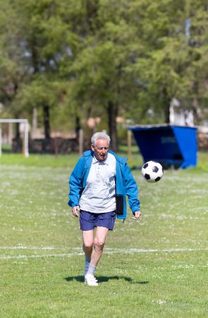 hombre viejo: Viejo hombre en setenta patear un bal�n de f�tbol en el campo